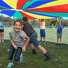 "Eric Bonzar—The Morning Journal<br /> Seventh-grader Kaylen Coleman, 12, races past fellow classmate Sandy Luke, 12, in an attempt to swap positions before they are caught under a collapsing parachute, during United Way's ""United We Sweat Field Day"" event, held at Midview High School's Ross Field, Sept. 13, 2016."