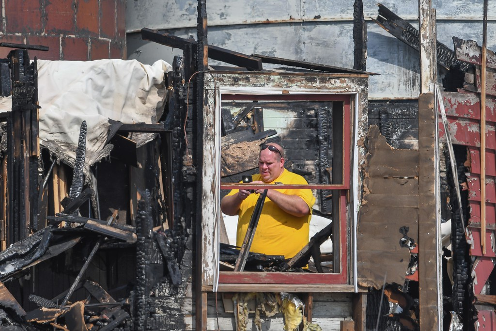 . Eric Bonzar�The Morning Journal <br> A property owner, who declined to give his name, uses his cell phone to capture images of  the damage to his building, Sept. 18, 2017. A fire, Sunday morning,  destroyed a 40,000 square foot structure and caused heat damage to several nearby buildings on Depot Street, in Wellington.