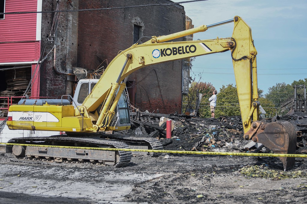 . Eric Bonzar�The Morning Journal <br> A property owner, who declined to give his name, assesses the damage to his building, Sept. 18, 2017, after a fire destroyed a 40,000 square foot structure and caused heat damage to several nearby buildings on Depot Street, in Wellington, Sunday morning.