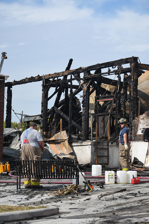 . Eric Bonzar�The Morning Journal <br> Wellington firefighters remained on scene, Sept. 18, 2017, after a fire destroyed a 40,000 square foot structure and caused heat damage to several nearby buildings on Depot Street, Sunday Morning.