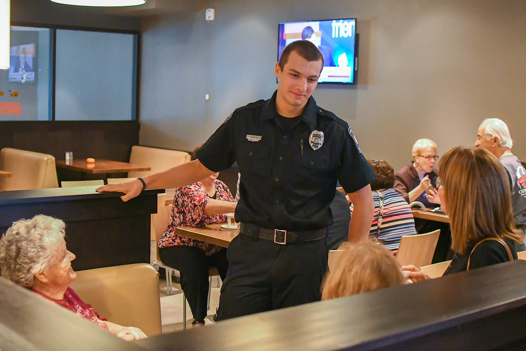 . Eric Bonzar�The Morning Journal<br> Nineteen-year-old dispatcher Nick Rennette converses with guests of the Avon Police Department\'s Coffee With a Cop gathering at Barry Bagels, 2100 Center Road, Oct. 4, 2017.  Rennette, a 2016 graduate of Avon High School, is furthering his education by studying police science at Lorain County Community College, and plans to enroll in the college\'s police academy when he turns 21; the age required to become a police officer, he said.