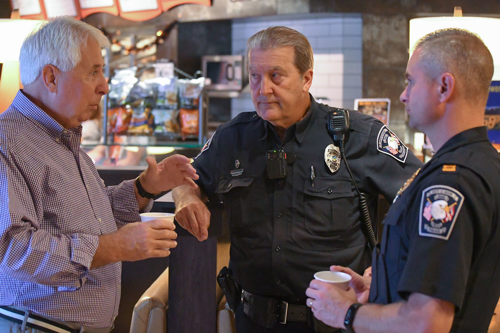 . Eric Bonzar�The Morning Journal<br> Avon police Capt. Larry Fischbach, right, and Officer Patrick Sullivan, center, converse with a guest of the department\'s Coffee With a Cop gathering at Barry Bagels, 2100 Center Road, Oct. 4, 2017.