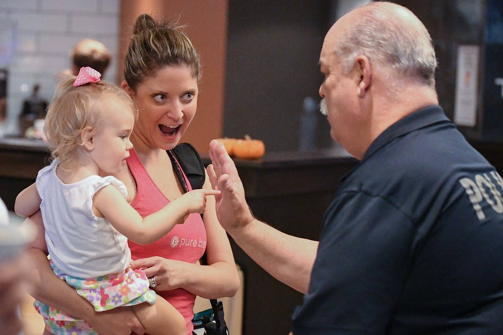 . Eric Bonzar�The Morning Journal<br> One-year-old Alexia Haggy gives School Resource Officer Jeffery Stanczyk a high-five during the Avon Police Department\'s Coffee With a Cop gathering at Barry Bagels, 2100 Center Road, Oct. 4, 2017. Alexia\'s mother, Claudia Haggy, of Avon said her family continuously donates food to the local police and fire departments, and is working to instill the value of helping others in her daughter.