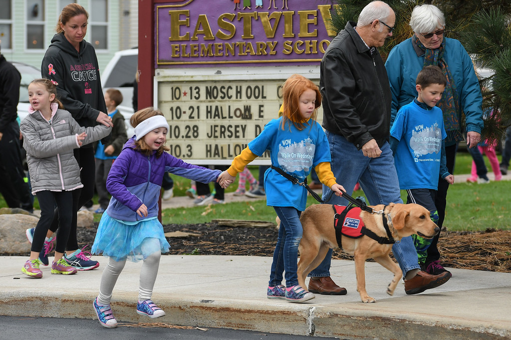 ". Eric Bonzar�The Morning Journal Seven-year-old Alyssa Jones and her service companion ""Mylo\"" walk in hand with classmate Kaidyn Luznar, 7, during Eastview Elementary School\'s Walk on Wednesdays (WOW) initiative, Oct. 26, 2016. Wednesday marked the final WOW of 2016, where students were encouraged to bring a friend to walk with and a pair of old shoes to donate to the nonprofit organization Planet Aid."