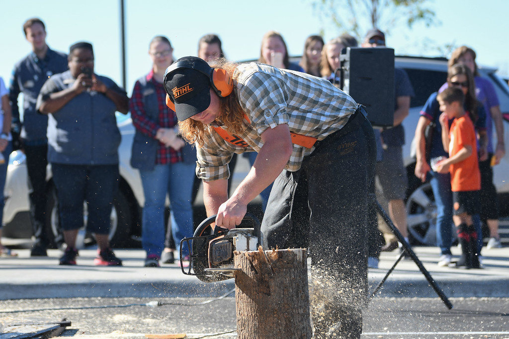 . Eric Bonzar�The Morning Journal<br> Spectators watch as Nick Hastedt, of Branson, Mo., saws through a log during the Duluth Trading Co.\'s lumberjack exhibition, Oct. 5, 2017. Duluth Trading Co. opened the doors on its 35455 Chester Road location, in Avon, on Thursday.