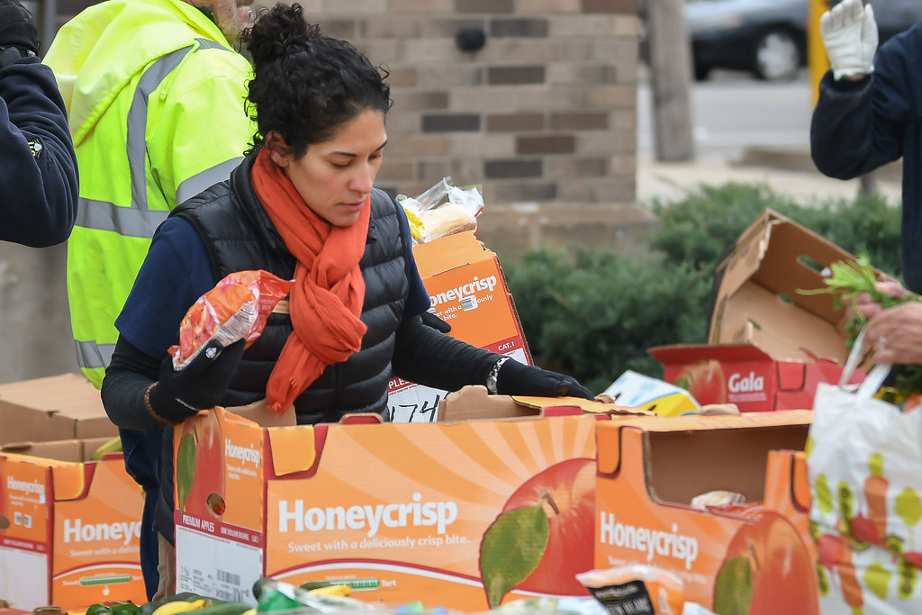 . Eric Bonzar�The Morning Journal<br> Second Harvest food Bank of North Central Ohio Program Coordinator Samantha Flores boxes carrots during the organization\'s mobile food pantry, held at El Centro de Servicios Sociales Inc., in Lorain, Nov. 16, 2017. Volunteers from Columbia Gas donated their time to help those in need, in conjunction with its state-wide, Week of Giving campaign.