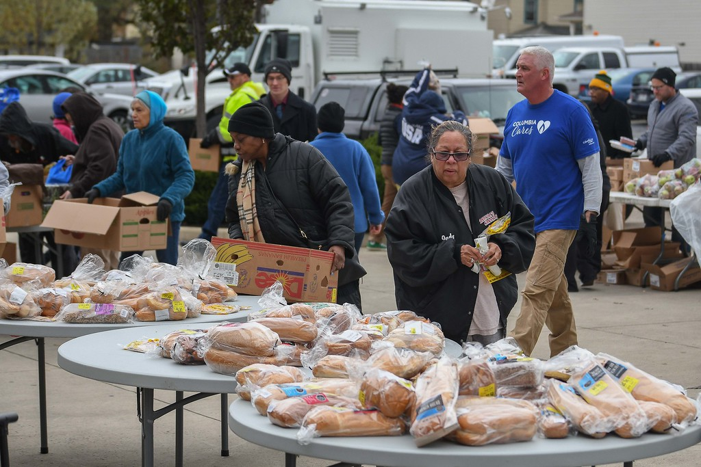 . Eric Bonzar�The Morning Journal<br> Patrons stock up on groceries during Second Harvest Food Bank of North Central Ohio\'s monthly, mobile food pantry, held at El Centro de Servicios Sociales Inc., in Lorain, Nov. 16, 2017. Volunteers from Columbia Gas donated their time to help those in need, in conjunction with its state-wide, Week of Giving campaign.