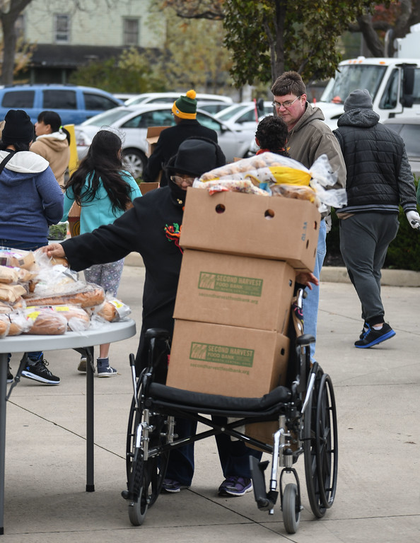 . Eric Bonzar�The Morning Journal<br> A patron uses her wheelchair to carry her groceries during Second Harvest Food Bank of North Central Ohio\'s monthly, mobile food pantry, held at El Centro de Servicios Sociales Inc., in Lorain, Nov. 16, 2017. Volunteers from Columbia Gas donated their time to help those in need, in conjunction with its state-wide, Week of Giving campaign.