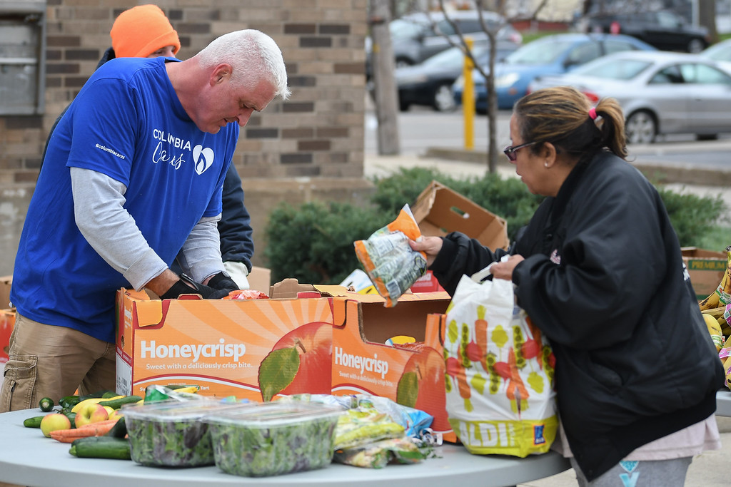 . Eric Bonzar�The Morning Journal<br> Columbia Gas Field Technician Scott Krugman boxes up groceries during Second Harvest Food Bank of North Central Ohio\'s monthly, mobile food pantry, held at El Centro de Servicios Sociales Inc., in Lorain, Nov. 16, 2017. Volunteers from Columbia Gas donated their time to help those in need, in conjunction with its state-wide, Week of Giving campaign.