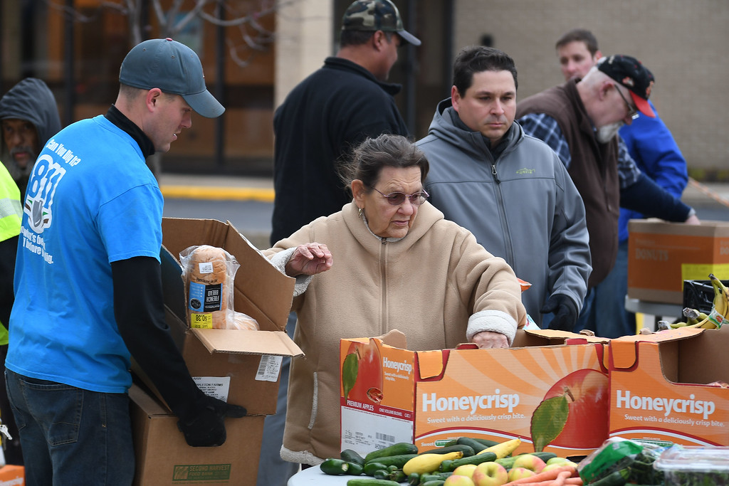 . Eric Bonzar�The Morning Journal<br> Columbia Gas Combination Technician Eric Newton, left, helps a patron with her groceries during Second Harvest Food Bank of North Central Ohio\'s monthly, mobile food pantry, held at El Centro de Servicios Sociales Inc., in Lorain, Nov. 16, 2017. Volunteers from Columbia Gas donated their time to help those in need, in conjunction with its state-wide, Week of Giving campaign.
