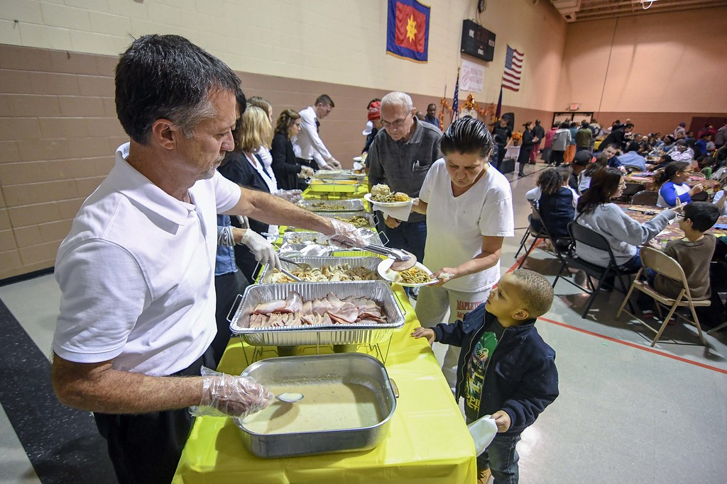 . Eric Bonzar�The Morning Journal<br> Mark Costello, with Amherst Sliman\'s Chrysler Jeep Dodge & Ram sales department, serves slices of ham during the Salvation Army of Lorain\'s Thanksgiving dinner, Nov. 21, 2017.