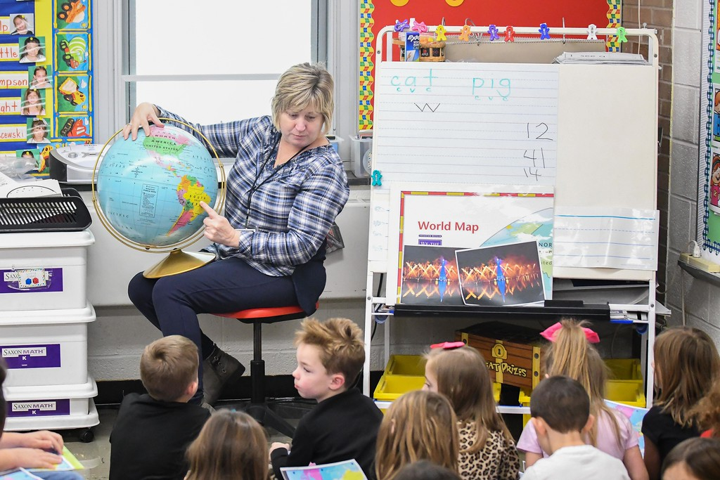 . Eric Bonzar�The Morning Journal<br> Westwood Elementary School Teacher Jill Stone shows her class where Brazil is on the globe, Dec. 4, 2017.  The Wellington kindergartners are traveling the world for the holidays, as they spend the month of December learning about holiday traditions in countries across the globe.