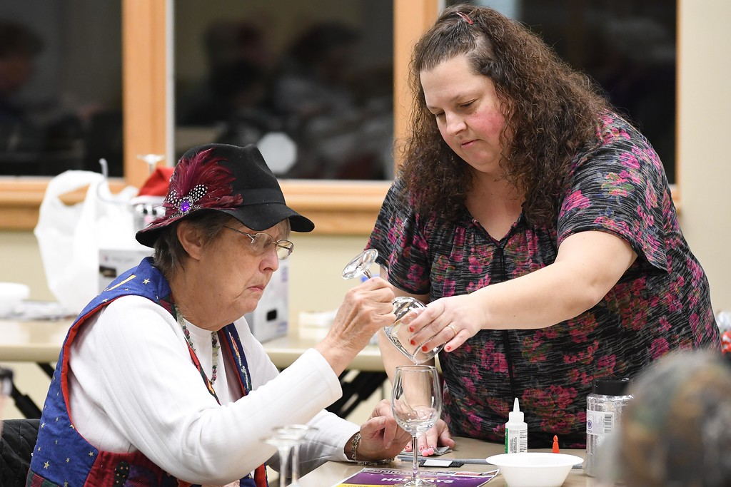 . Eric Bonzar�The Morning Journal<br> Instructor Liz Guilkey, right, goes over her glass glittering techniques with Janet Nelson, of Brooklyn, during an adult holiday crafting session at the Lorain Public Library System\'s South Branch, Dec. 5, 2017.