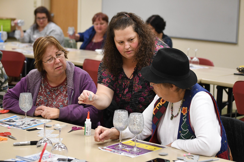 . Eric Bonzar�The Morning Journal<br> Liz Guilkey, center, goes over how to create felt mouse ears with Sharon Kross, of North Olmsted (right) and Janet Nelson, of Brooklyn, during an adult holiday crafting session at the Lorain Public Library System\'s South Branch, Dec. 5, 2017.
