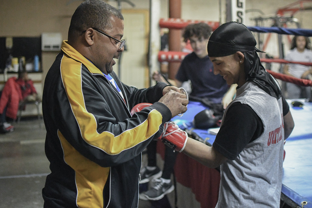 . Eric Bonzar�The Morning Journal<br> Fifteen-year-old Shackbel Torres, of Lorain, gets his gloves laced up by trainer Freddie Osorio at United Boxing Club, in Lorain, Dec. 6, 2017.