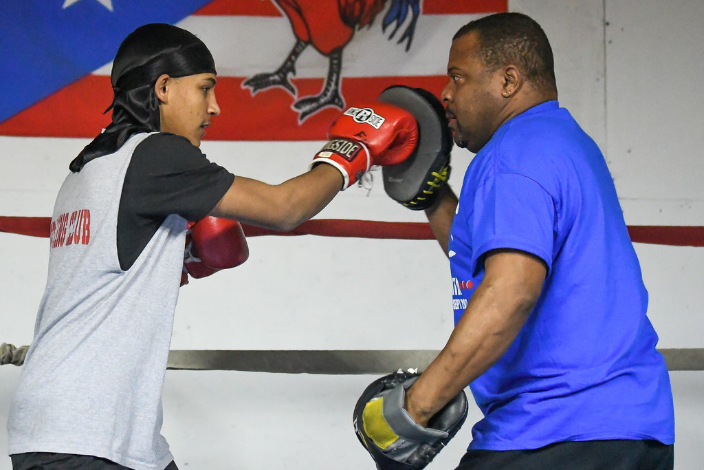 . Eric Bonzar�The Morning Journal<br> Fifteen-year-old Shackbel Torres, of Lorain, works on his right cross with trainer Freddie Osorio at United Boxing Club, in Lorain, Dec. 6, 2017.