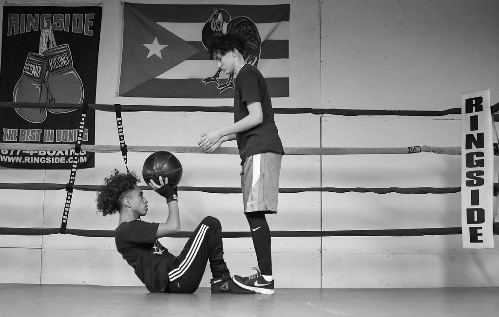 . Eric Bonzar�The Morning Journal<br> Sixteen-year-old Giovanni Rayes (on the mat) and 15-year-old Nya Smith, work out with the medicine ball at United Boxing Club, in Lorain, Dec. 6, 2017.