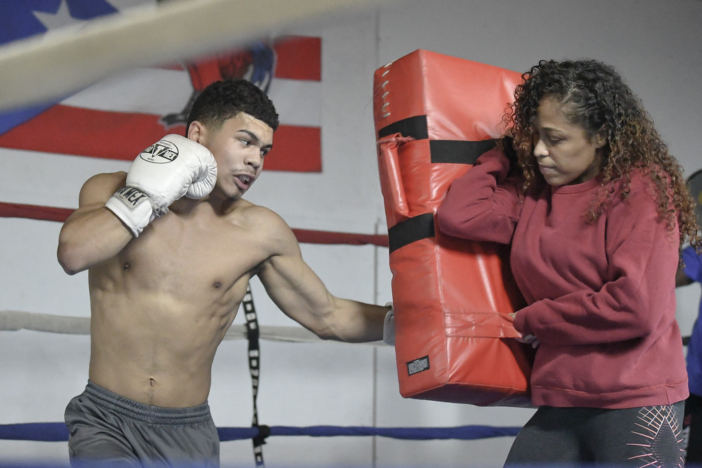 . Eric Bonzar�The Morning Journal<br> Mother and son team Amarilis Burgos and 17-year-old Luis Burgos get in a workout at United Boxing Club, in Lorain, Dec. 6, 2017.