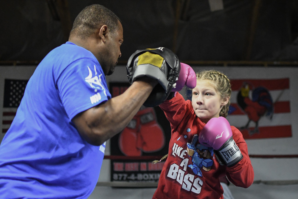 . Eric Bonzar�The Morning Journal<br> Ten-year-old Aubrey Gyorfi works on her right cross with trainer Freddie Osorio at United Boxing Club, in Lorain, Dec. 6, 2017.