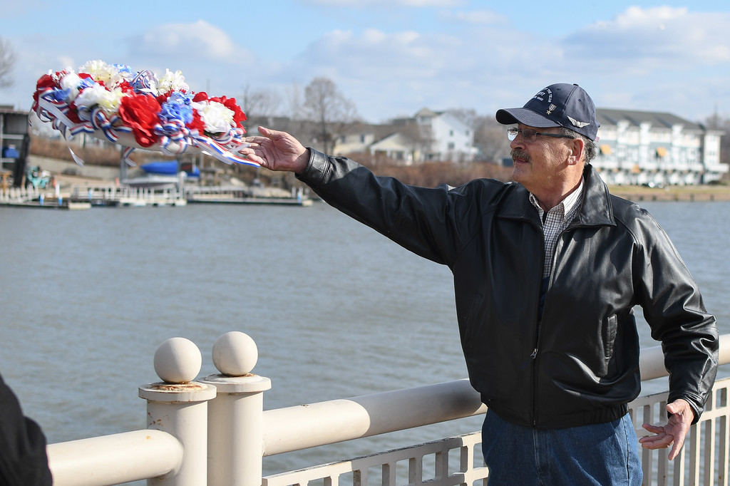. Eric Bonzar�The Morning Journal<br> Joe Horvath, U.S. Army veteran and 2017 Veteran of the Year, tosses a wreath into the water in remembrance, concluding Lorain AMVETS Post No. 47\'s  Honoring Pearl Harbor Day ceremony held at Black River Landing, Dec. 7, 2017.