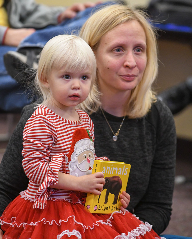 . Eric Bonzar�The Morning Journal<br> Two-year-old Heather Wilson sits with her mom, Lauren Wilson, of Avon, and listens to a story read by Library Associate Kelsey DeCoste during Lorain Public Library System North Ridgeville Branch\'s Family Fun Story Time, Dec. 11, 2017.