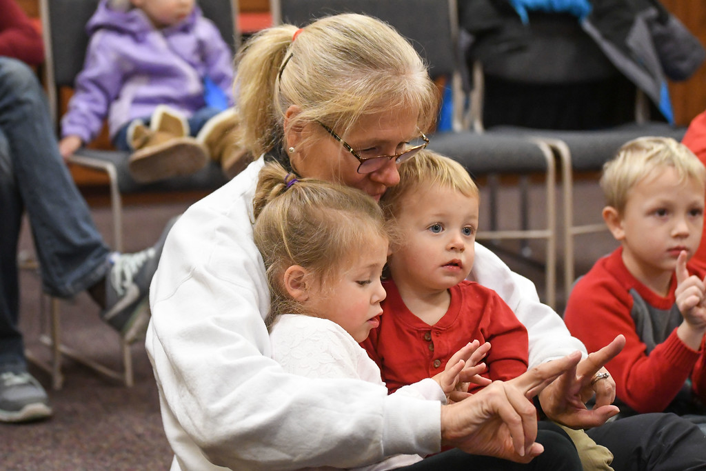 ". Eric Bonzar�The Morning Journal<br> Sue Poultney, of North Ridgeville, shows her grandchildren Isla Wheaton, 3, and 18-month-old Dax Wheaton how to make a ""W\"" with their fingers  during Lorain Public Library System North Ridgeville Branch\'s Family Fun Story Time, Dec. 11, 2017."