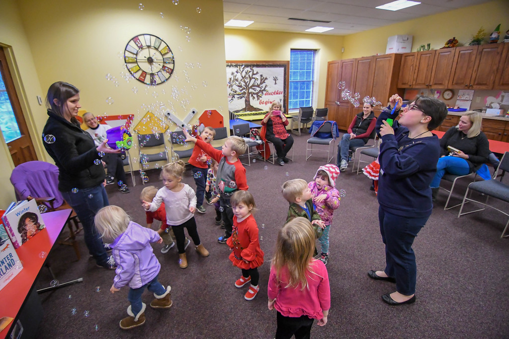 . Eric Bonzar�The Morning Journal<br> Children dance and pop bubbles during Lorain Public Library System North Ridgeville Branch\'s Family Fun Story Time with Youth Services Librarian Ally Morgan, left, and Library Associate Kelsey DeCoste, Dec. 11, 2017.