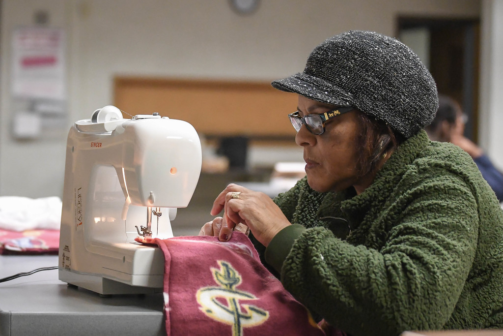 . Eric Bonzar�The Morning Journal<br> Laverne Calhoun, of Lorain, sews a Cleveland Cavaliers blanket during a Sewing Club session at Lorain Public Library System\'s Main Branch, Dec. 12, 2017.