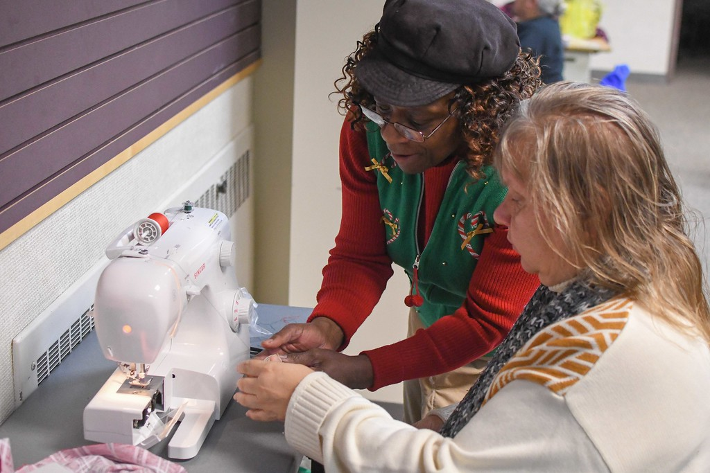 . Eric Bonzar�The Morning Journal<br> Instructor Charlene Jones shows Sherri Bennett, of Lorain, how to efficiently move thread, from a spool onto a bobbin, during a Sewing Club session at Lorain Public Library System\'s Main Branch, Dec. 12, 2017.
