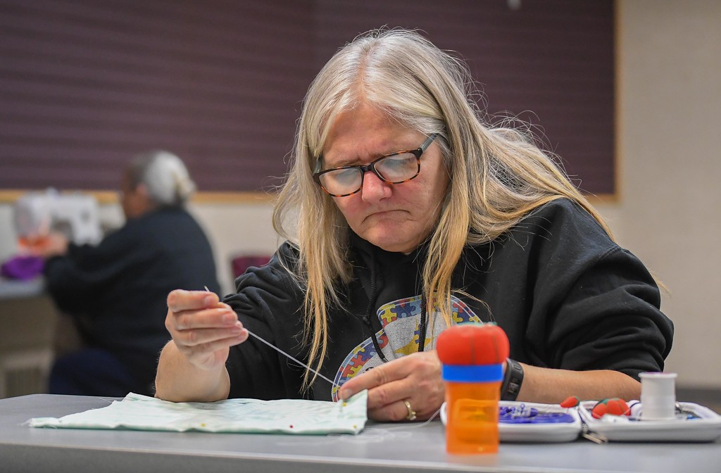. Eric Bonzar�The Morning Journal<br> New club member Annette Booth, of Lorain, works on stitching material  together by hand during a Sewing Club session at Lorain Public Library System\'s Main Branch, Dec. 12, 2017.  Instructor Charlene Jones said stitching by hand is a prerequisite, of sorts, for new students before graduating to the sewing machine.