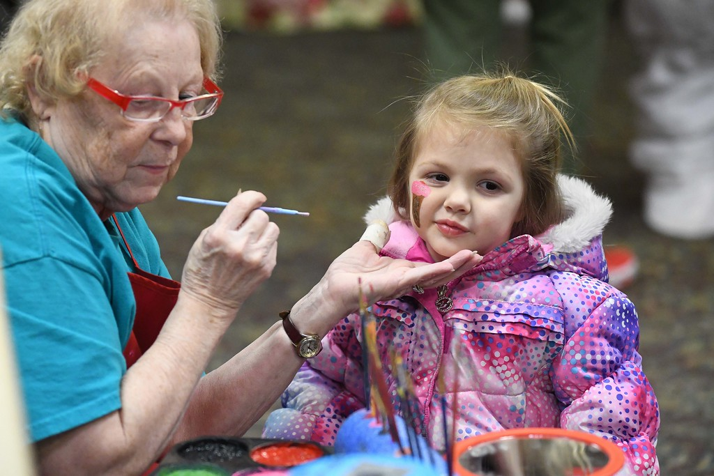 . Eric Bonzar�The Morning Journal<br> Volunteer Christine Burman, of Amherst, paints a pink ice cream cone onto the cheek of 3-year-old Lila Sandell during Main Street Amherst\'s Lolly the Trolley event, Dec. 13, 2017.