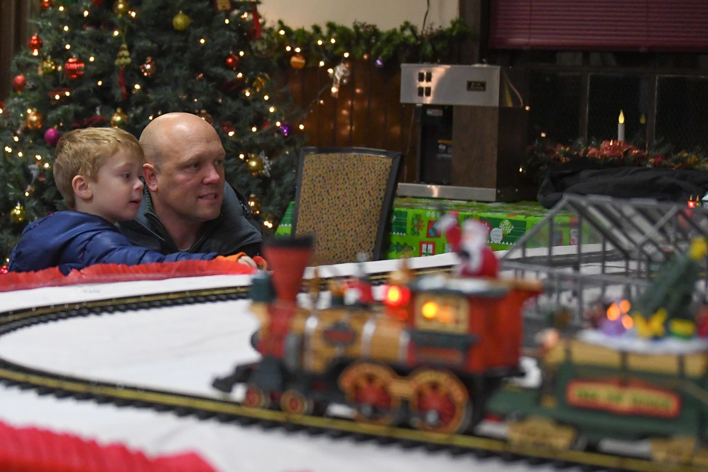 . Eric Bonzar�The Morning Journal<br> Todd Ramsey and his 3-year-old son Evan, of North Ridgeville, watch Rich Papay\'s holiday-themed train set go around the track during Main Street Amherst\'s Lolly the Trolley event, Dec. 13, 2017.