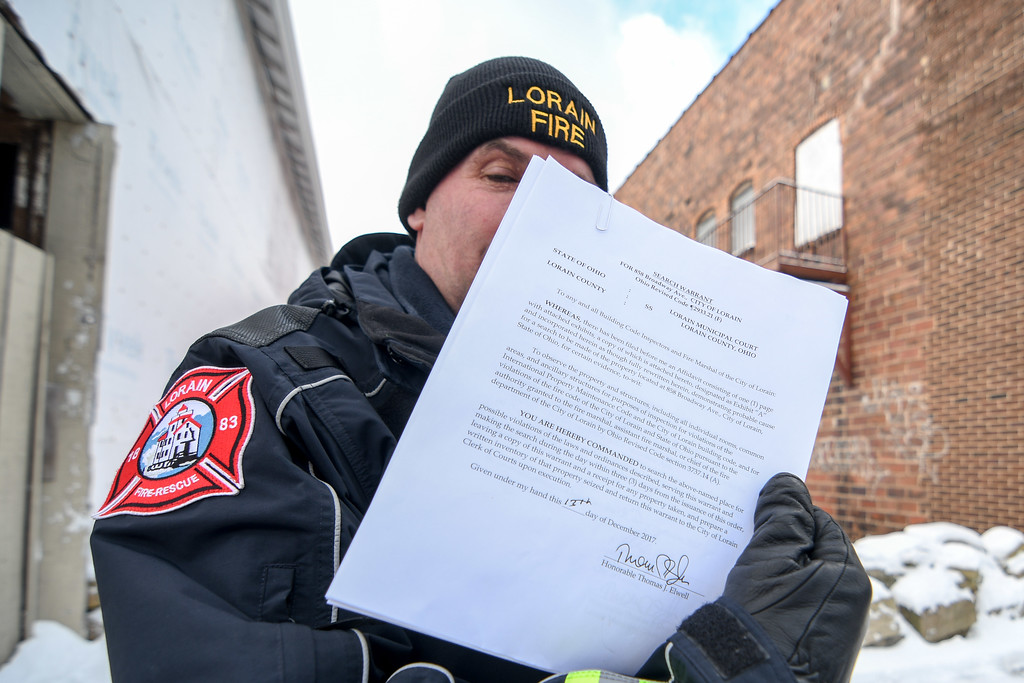 . Eric Bonzar�The Morning Journal<br> With warrant in hand, Lorain Fire Department Lt. Steven Bajcer prepares to enter Nelis Wallpaper, 858 Broadway Ave., Dec. 14, 2017. The building and its owner have currently come under fire from Lorain Growth Corp., and others invested in the revitalization of downtown Lorain, who have called upon the city�s building inspectors to hold property owners accountable for the deteriorating conditions of their buildings located along Broadway.