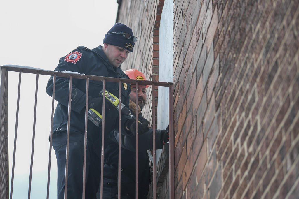 . Eric Bonzar�The Morning Journal<br> Assistant Fire Chief Christopher Radman and Housing Inspector Eric Elmi re-secure a piece of plywood covering a second story window of 852 Broadway Ave., Dec. 14, 2017. The pair were on Broadway to execute a warrant to conduct an inspection of the property and the adjacent Nelis Wallpaper building. Recently, dilapidated buildings and their owners have come under fire from Lorain Growth Corp., and others invested in the revitalization of downtown Lorain, who have called upon the city�s building inspectors to hold property owners accountable for the deteriorating conditions of their buildings located along Broadway.
