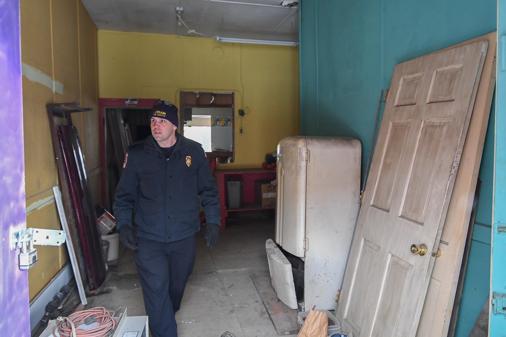 . Eric Bonzar�The Morning Journal<br> Assistant Fire Chief Christopher Radman inspects a first floor electrical box inside of  Nelis Wallpaper, 858 Broadway Ave., Dec. 14, 2017. The building and its owner have currently come under fire from Lorain Growth Corp., and others invested in the revitalization of downtown Lorain, who have called upon the city�s building inspectors to hold property owners accountable for the deteriorating conditions of their buildings located along Broadway.