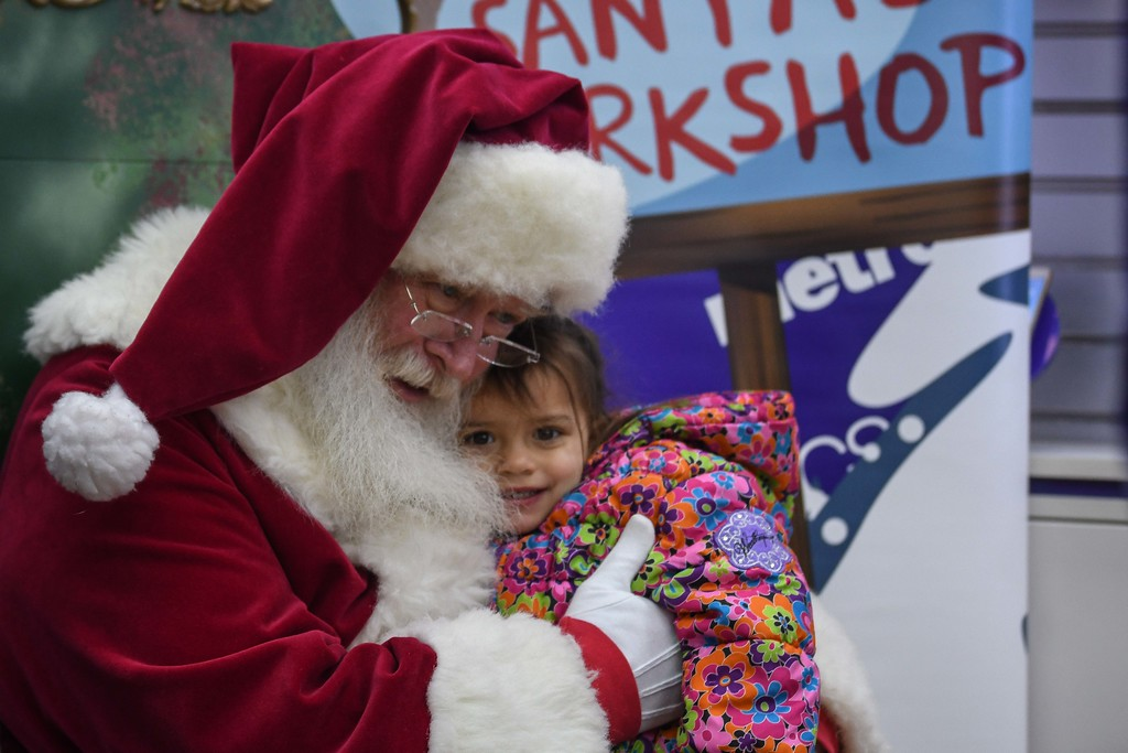 ". Eric Bonzar�The Morning Journal<br> Two-year-old Kadence Swiger gets a hug from ""Santa\"" during Metro PCS 225 E. 42nd St. location\'s customer appreciation holiday party, Dec. 15, 2017."