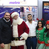 "Eric Bonzar—The Morning Journal<br> District Manager Momo Alnazer (left of Santa) and Owner Moe Haq (right of Santa) pose for a photo with ""Santa"" and his ""elves"" during Metro PCS' customer appreciation holiday party, Dec. 15, 2017, at the cellular service's 225 E.42nd St. location."