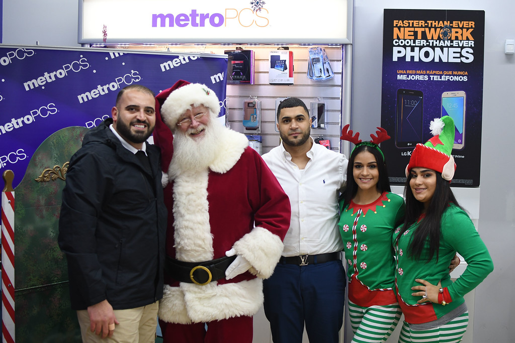 ". Eric Bonzar�The Morning Journal<br> District Manager Momo Alnazer (left of Santa) and Owner Moe Haq (right of Santa) pose for a photo with ""Santa\"" and his \""elves\"" during Metro PCS\' customer appreciation holiday party, Dec. 15, 2017, at the cellular service\'s 225 E.42nd St. location."