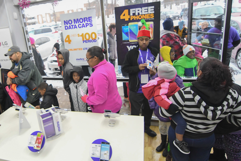 . Eric Bonzar�The Morning Journal<br> Families pack Owner Moe Haq\'s 225 E. 42nd St. Metro PCS location to benefit from the store owner\'s generosity during the store\'s customer appreciation holiday party, Dec. 15, 2017.