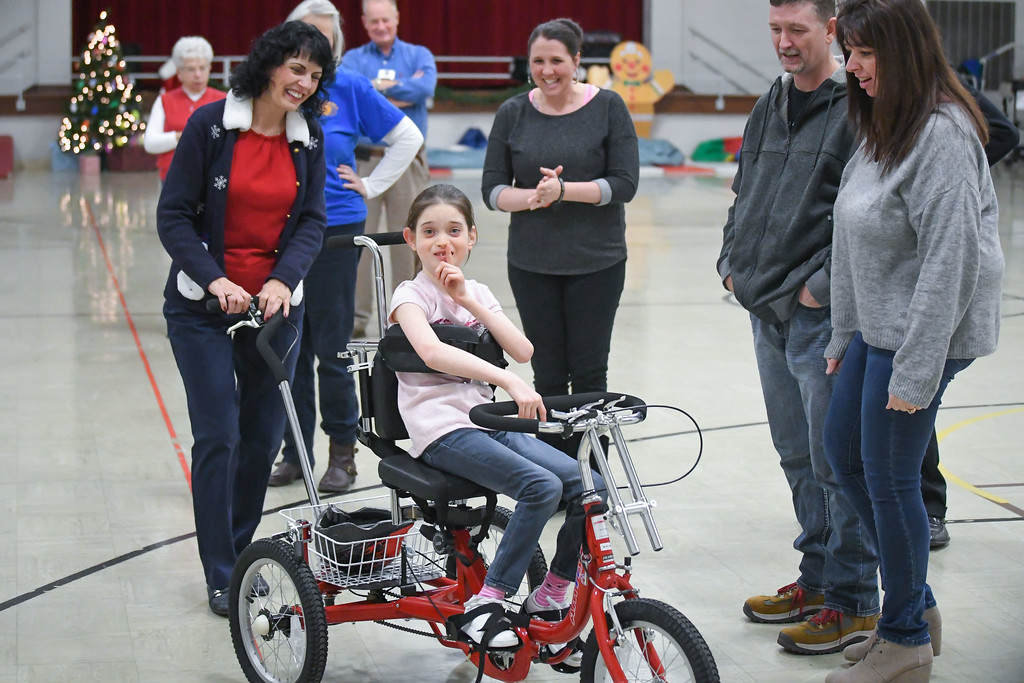 . Eric Bonzar�The Morning Journal<br> Ten-year-old Makenzie Dvorscak takes a spin on her new Amtryke therapeutic tricycle with North Ridgeville Kiwanis Club member Cindy Hemsoth as her parents and staff of Murray ridge School look on, Dec. 19, 2017.