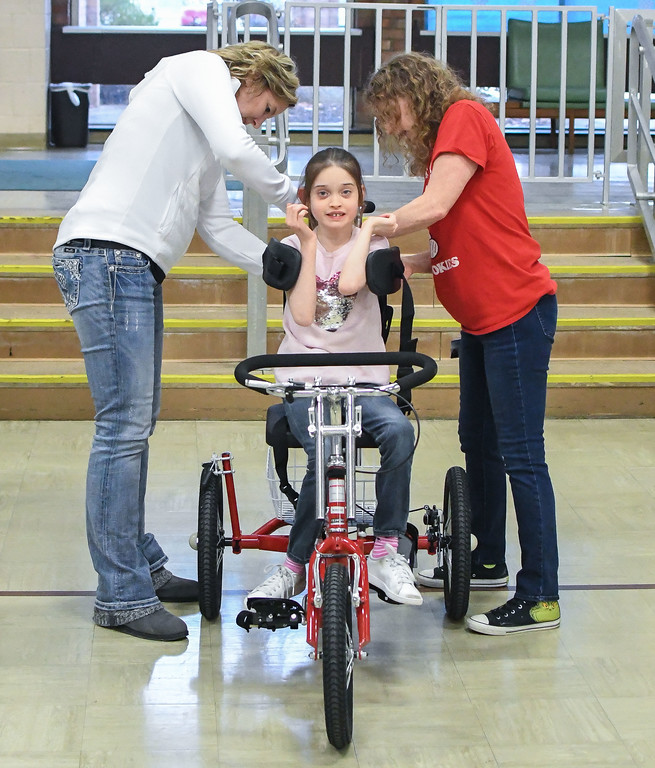 . Eric Bonzar�The Morning Journal<br> Ten-year-old Makenzie Dvorscak prepares to take her first ride, as she is secured in her new Amtryke therapeutic tricycle by physical therapist Becky Barmer, left, and teacher Vickie Nagy, Dec. 19, 2017. Members of the North Ridgeville Kiwanis Club surprised the Murray Ridge School student with her new ride, Tuesday afternoon, in the school\'s gymnasium.