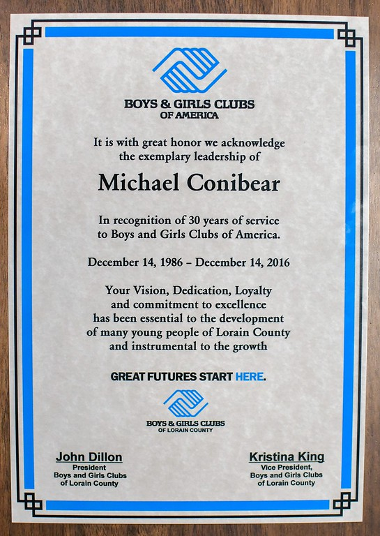 . Eric Bonzar�The Morning Journal During their appreciation luncheon, Lorain County Boys and Girls Clubs staff presented Executive Director Mike Conibear with a plaque, recognizing his 30 years of service with the organization, Dec. 22, 2016.
