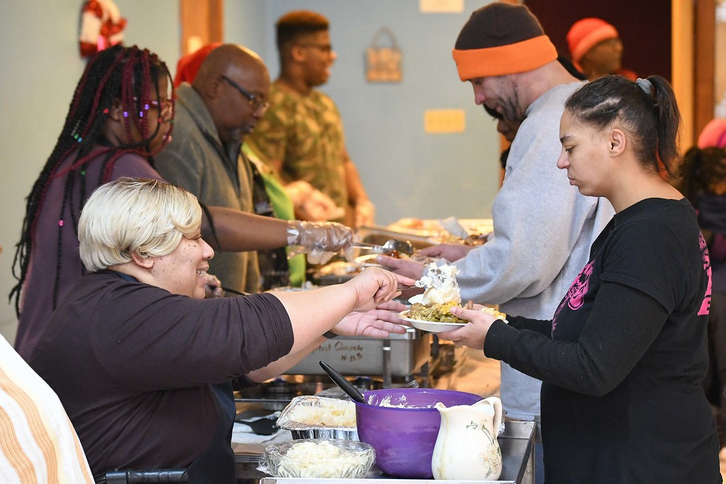 . Eric Bonzar�The Morning Journal<br> Marcella Bryant, and fellow members of Second Baptist Church, serve a hot lunch to guests during the organization\'s Kwanzaa celebration, in Lorain, Dec. 26, 2017.