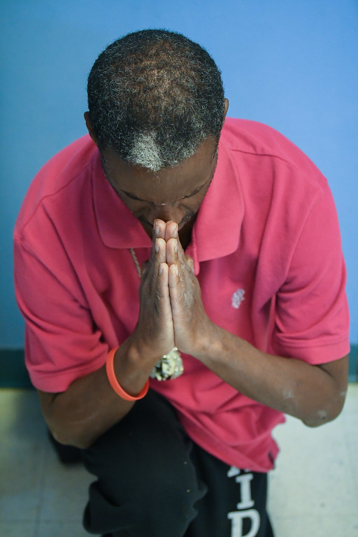 """. Eric Bonzar�The Morning Journal<br> Carl Jeans Jr., self-proclaimed \""""number one praiser,\"""" takes a moment for prayer during Second Baptist Church\'s Kwanzaa celebration, in Lorain, Dec. 26, 2017."""