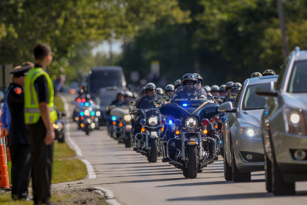 . Eric Bonzar�The Morning Journal Mourners and supporters lined the sides of North Ridge Road, waving signs and American flags as the funeral procession for Ohio State Highway Patrol Trooper Kenneth Velez arrives at Calvary Cemetery, Sept. 22, 2016.