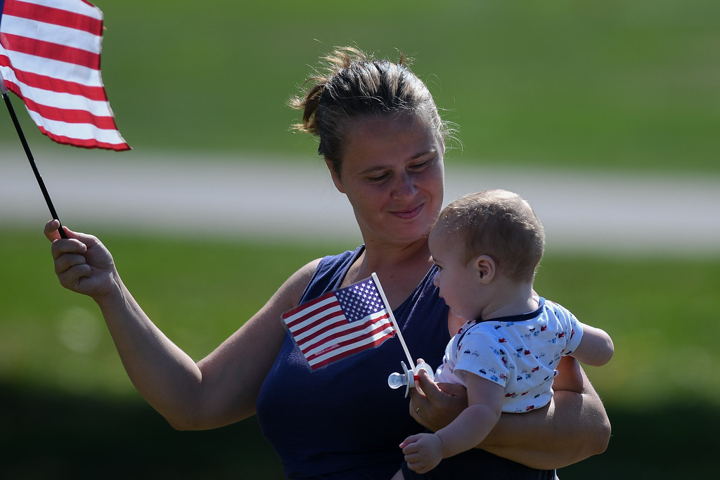 . Eric Bonzar�The Morning Journal A mother and her child stand along the funeral procession for Ohio State Highway Patrol Trooper Kenneth Velez, waving American flags, Sept. 22, 2016.