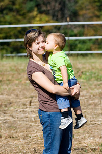 Mom gets a break for affection in the middle of a pumpkin patch.
