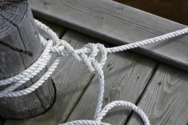 Ropes and a wooden bollard in a harbor