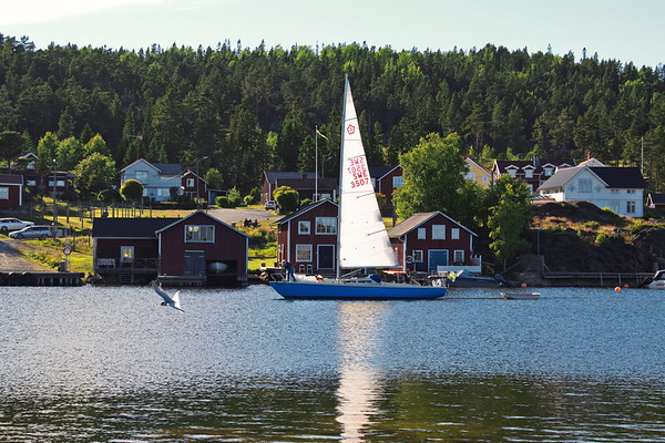 A sailboat is entering a traditional fishing village in Sweden