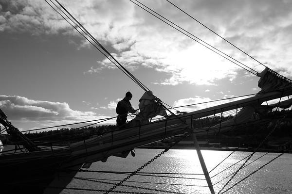 Skepp Trekronor i Örnsköldsvik 2013 -  Sailor losening a sail - monochrome
